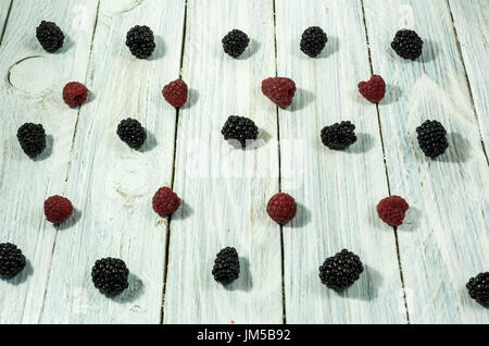 Blackberry and raspberries. are arranged in a row. Top view. Berries on a white background. - Stock Photo