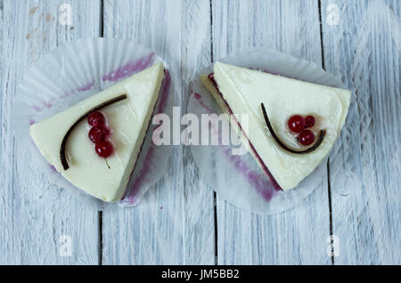 White cheesecake with red currant. Flat lay White wooden background. - Stock Photo