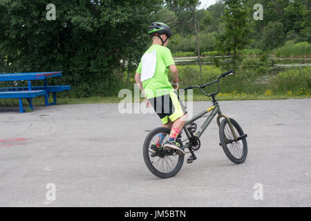 Teenage boy doing tricks on bicycle during BMX competition at Omemee Days - Stock Photo