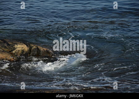 Close up detail shot of Atlantic Ocean waves crashing against rocks - Stock Photo
