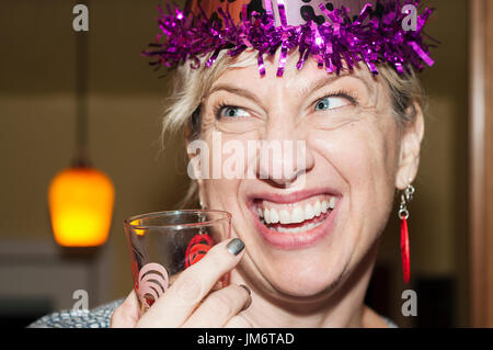 A woman wearing a party hat at a birthday celebration. - Stock Photo