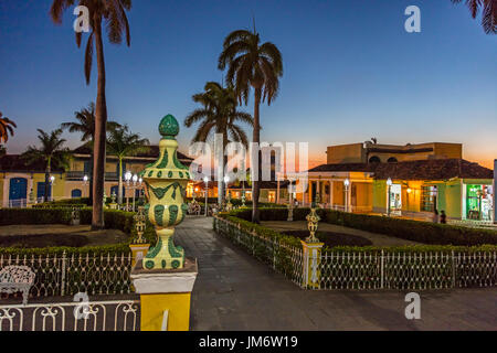 Palm trees and historic buildings on the PLAZA MAYOR at dusk - TRINIDAD, CUBA - Stock Photo