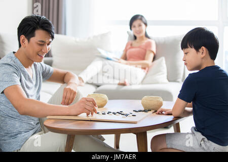 Little Chinese boy playing the game of Go with father - Stock Photo