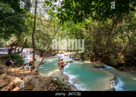 LUANG PRABANG, LAOS - MARCH 10, 2017: Tourists walking in the beautiful Kuang Si Falls in Laos, close to Luang Prabang. - Stock Photo