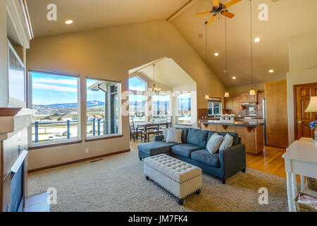 Large living or great room in a residential home with vaulted ceilings formal dining and view from a wall of windows - Stock Photo