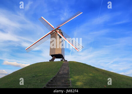 Windmill on green hill on a sunny day. Retro windmill on blue sky background. Landmark of Bruges. - Stock Photo
