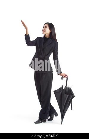 young asian businesswoman with folded black umbrella, studio shot, isolated on white background. - Stock Photo