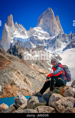 Male trekker resting on the rock in front of the stunning and impressive Mount Fitz Roy near El Chalten in Patagonia, - Stock Photo