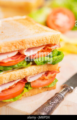 A club sandwich on a rustic table in bright light. - Stock Photo