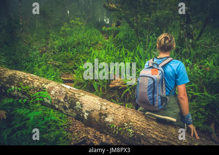 Girl resting on a fallen tree log the jungle path to the summit of Gunung Rinjani volcano in Lombok, Indonesia - Stock Photo