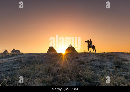 Man and horse silhouette on the background of valley at Cappadocia,Anatolia,Turkey.The great tourist attraction - Stock Photo