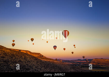 Colorful hot air balloons flying over the valley at Cappadocia,Anatolia,Turkey.The great tourist attraction of Cappadocia - Stock Photo