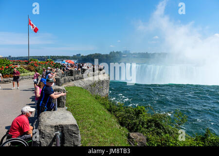 Visitors to Niagara Falls watch the Canadian Horseshoe Falls from a viewpoint. Spray from the Falls is in the air - Stock Photo