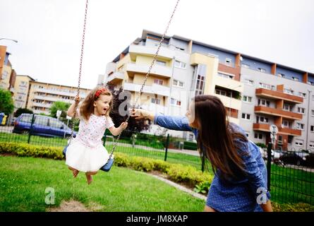 Young mother plays in the playground with the little daughter. Woman shakes the baby on a swing. Serene summer day. - Stock Photo