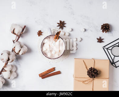 Hot cocoa with marshmallows, cotton branch and pine cones on marble background, top view - Stock Photo