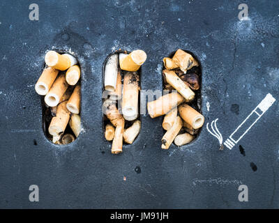 Stubbed out cigarette butts - Stock Photo