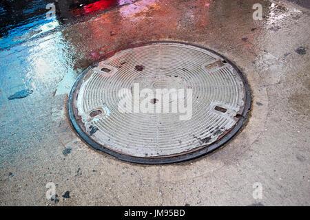 conedison manhole cover in the rain New York City USA - Stock Photo