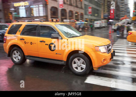 ford escape hybrid suv new york yellow taxi cab crossing times square in the rain New York City USA - Stock Photo