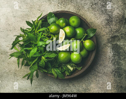 Flatlay of fresh limes and mint in wooden plate - Stock Photo