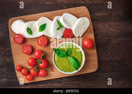 An overhead photo of buffalo mozzarella cheese with cherry tomatoes, green basil leaves, the ingredients of the - Stock Photo