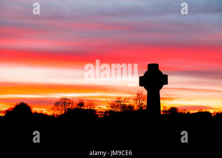 Durham landscape: iconic stone Celtic cross standing in the graveyard at Durham Cathedral, County Durham at sunset - Stock Photo