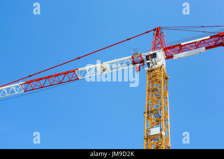 Low angle view of a tower crane with yellow tower section and a red and white jib and counter-jib sections against - Stock Photo