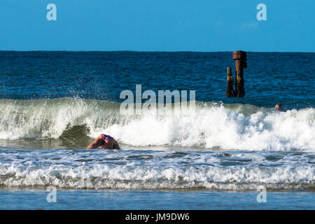 Bottoms up at 'The wreck' off Belongil beach, Byron bay, NSW, Australia. - Stock Photo
