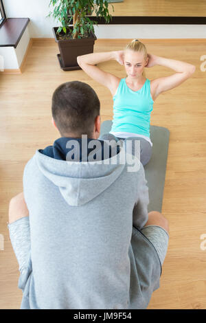 Personal trainer helping young attractive woman doing crunches in the gym - Stock Photo
