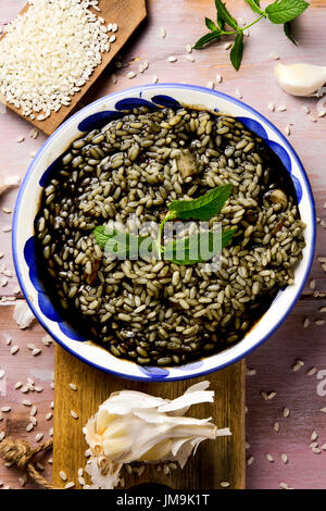 high-angle shot of a white and blue ceramic plate with spanish arroz negro or black paella, a variation of the seafood - Stock Photo