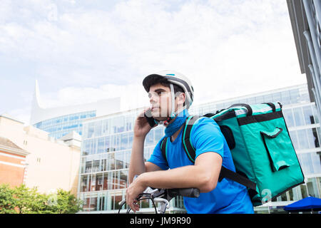 Courier On Bicycle Delivering Food In City Using Mobile Phone - Stock Photo
