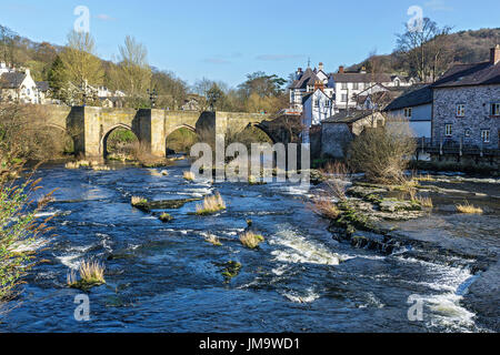 River Dee flowing through the centre of Llangollen showing the Dee Bridge a scheduled ancient monument Denbighshire - Stock Photo
