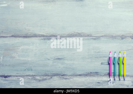 Set of colored pens on blue wooden background, flat lay - Stock Photo