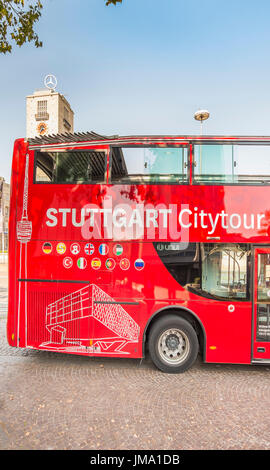 red stuttgart city tours bus, tower of central station with mercedes star in background, stuttgart, baden-wuerttemberg, - Stock Photo