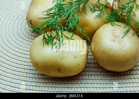 Potatoes and dill on a wicker napkin - Stock Photo