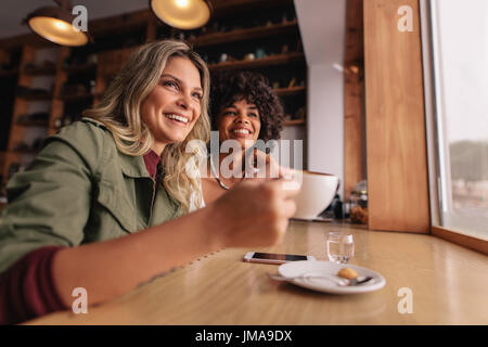 Two young woman sitting at cafe and having coffee. Female friends drinking coffee at restaurant. - Stock Photo