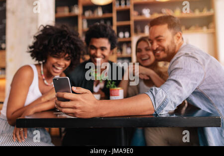 Young men and women sitting at cafe table and taking a self portrait with mobile phone. Multiracial group of friends - Stock Photo