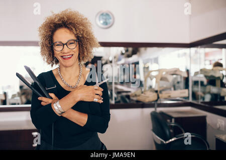 Professional hair stylist holding a hair straightener and scissors. Woman hairdresser in happy mood at the salon. - Stock Photo