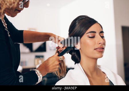 Woman hairdresser using a hairbrush for a hairdo at the salon. Young woman getting a stylish hairdo done at salon. - Stock Photo