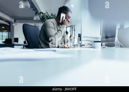 African man talking on mobile phone. Businessman sitting in modern office using cellphone. - Stock Photo