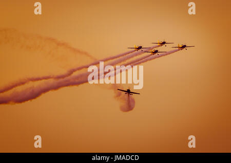 Airplanes on airshow. Aerobatic team performs flight at air show. Flight in twilight. - Stock Photo