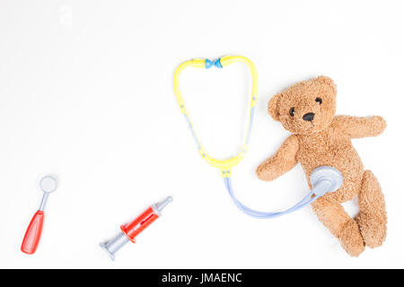 Teddy bear with toy stethoscope and toy medicine tools on a white background. - Stock Photo