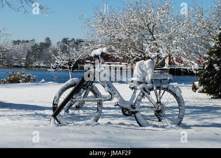 Snow covered bicycle - Stock Photo