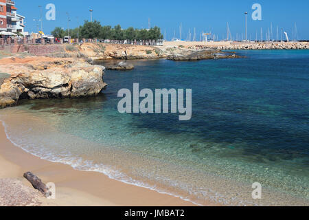 Sandy beach and bay in city. Porto-Torres, Italy - Stock Photo