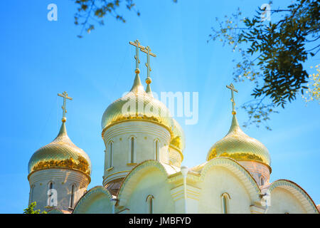 Golden domes of the Orthodox church against the blue sky on a sunny day. - Stock Photo