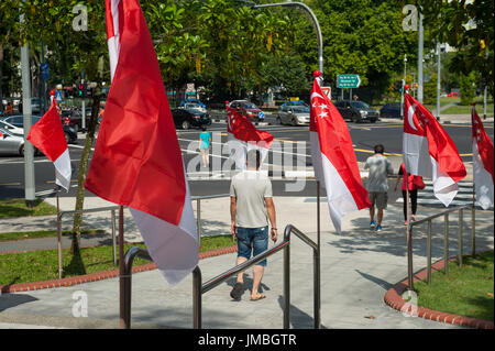 23.07.2017, Singapore, Republic of Singapore, Asia - National flags are waving at a road junction in front of a - Stock Photo