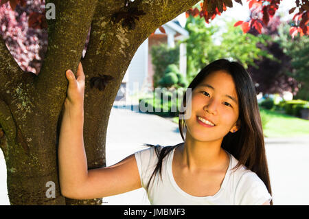 Portrait Young Ethnic Asian under Blooming Plum Tree - Stock Photo