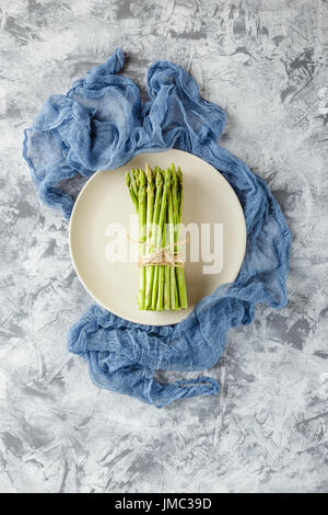 Bundle of raw asparagus on plate on light background. Top view - Stock Photo