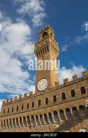Italy, Florence - November 06 2016: view of the clock tower fragment of the Old Palace with blue sky on November - Stock Photo