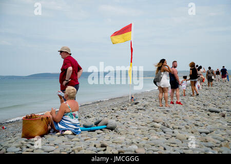 British holidaymakers on a pebble beach on a cloudy, windy day - Stock Photo
