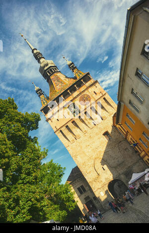 View to the clock tower in Sighisoara, Romania; the city is considered the most beautiful and well preserved inhabited - Stock Photo